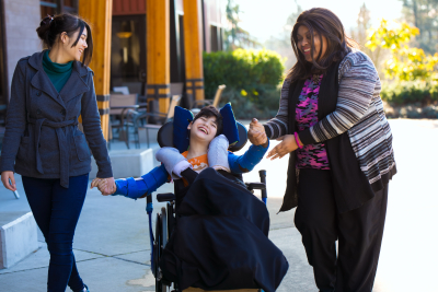 two woman guiding a boy on wheelchair