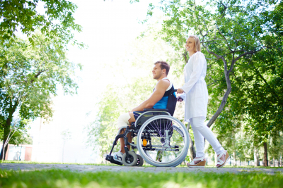 woman guiding a man on a wheelchair